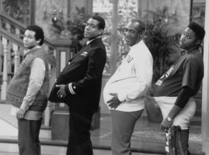 "THE COSBY SHOW -- ""The Day the Spores Landed"" Episode 8 -- Air Date 11/09/1989 -- Pictured: (l-r) Geoffrey Owens as Elvin Tibideaux, Joseph C. Phillips as Lt. Martin Kendall, Bill Cosby as Dr. Heathcliff 'Cliff' Huxtable, Malcolm-Jamal Warner as Theodore 'Theo' Huxtable (Photo by NBC/NBCU Photo Bank via Getty Images)"